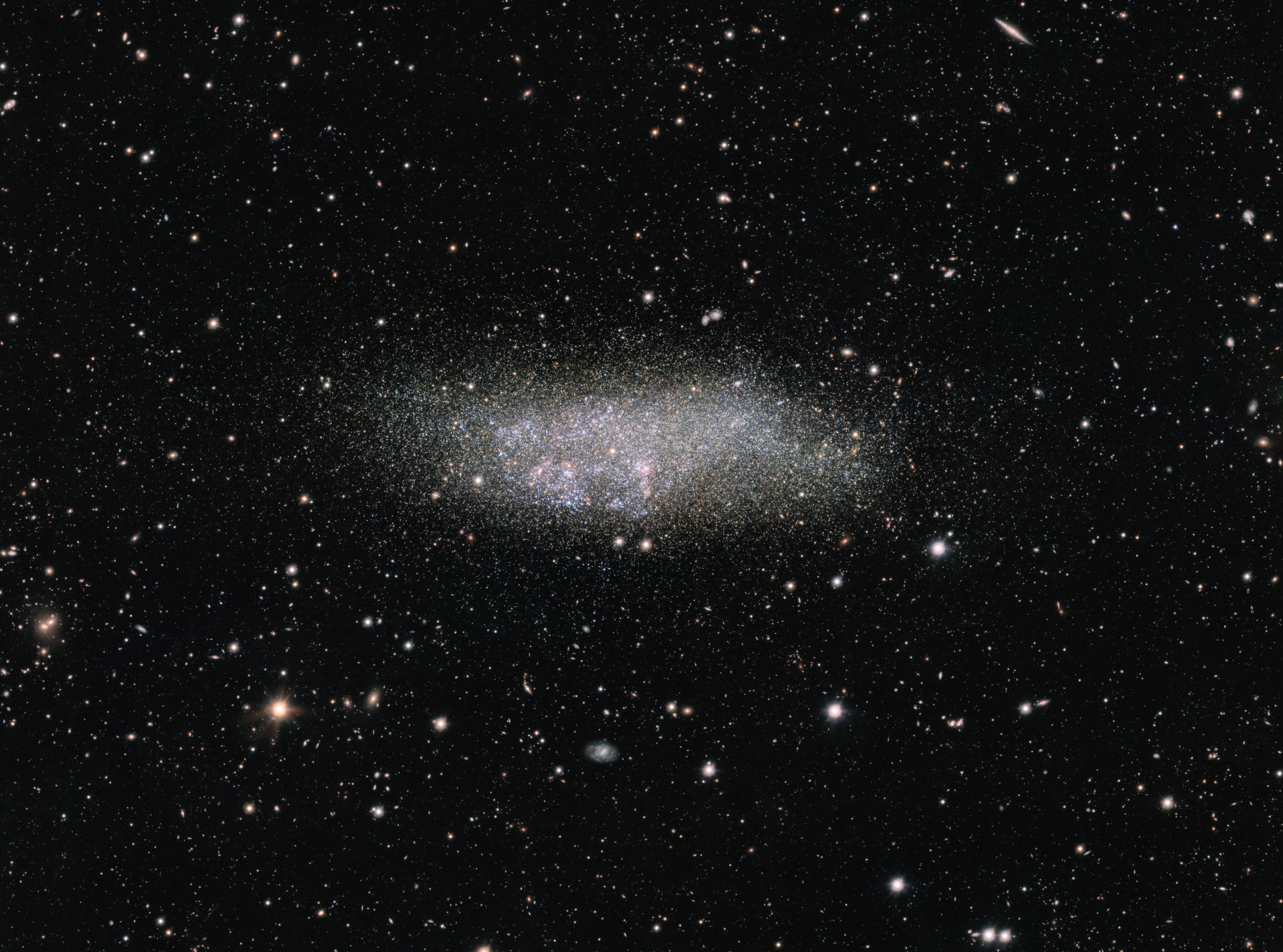 This image, captured by ESO's OmegaCAM on the VLT Survey Telescope, shows a lonely galaxy known as Wolf-Lundmark-Melotte, or WLM for short. Although considered part of our Local Group of dozens of galaxies, WLM stands alone at the group's outer edges as one of its most remote members. In fact, the galaxy is so small and secluded that it may never have interacted with any other Local Group galaxy — or perhaps even any other galaxy in the history of the Universe.